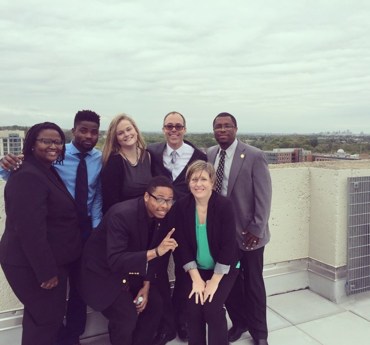 Seven people stand on a rooftop, smiling for a portrait. They wear professional clothing, including blazers.