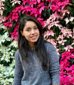 A young woman with long black hair wears a grey sweater smiles at the camera with a wall of pink and white flowers.
