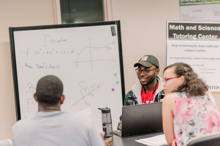 "Three students gather around a table, talking, with math equations written on a board. A sign reads ""Math and Science Tutoring Center"""