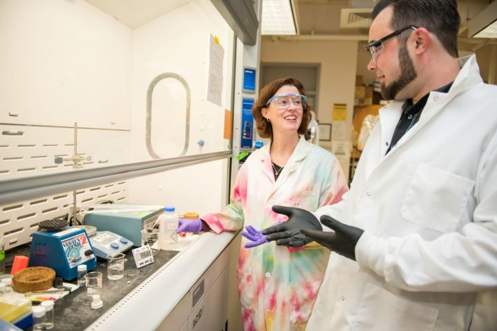 Woman with auburn hair stands with a man with dark bears in a lab. She wears a tie dyed lab coat and he wears a white lab coat.