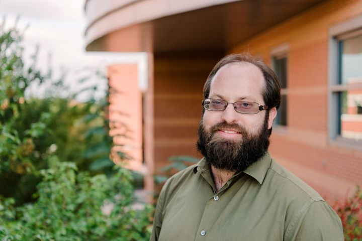 Portrait of a middle-aged white man with full beard. He wears a green dress shirt and wire-framed glasses. He stands in front of a brick building and plants.