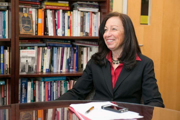 Portrait of middle-aged white woman with long, dark hair. She sits at a desk in an office, with books in the background. She wears a red collared shirt and black suit jacket.