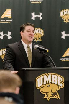 Middle-aged man with short, dark hair stands at a podium. The podium has a UMBC Athletics logo, as does a banner behind him. He wears a suit with yellow and black tie.