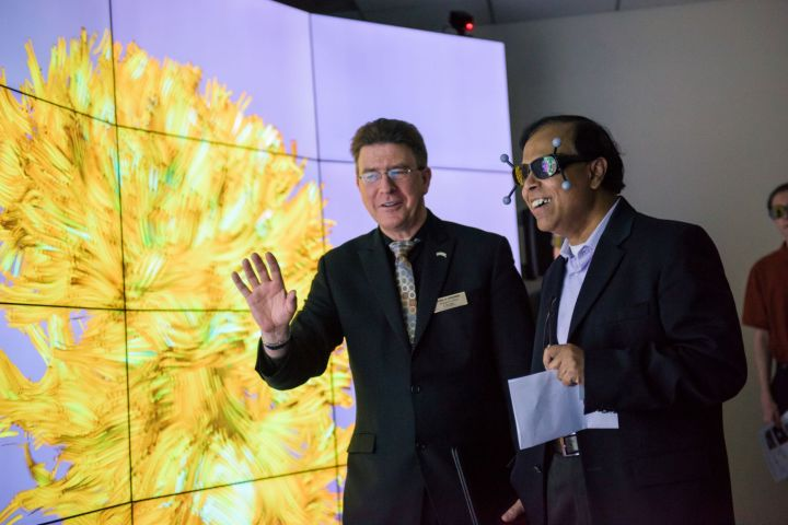 Two men in students stand in front of a brightly lit screen. One gestures while the other wears VR goggles with amazed facial expression.