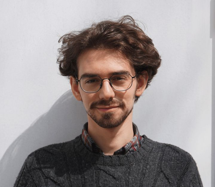 Outdoor portrait of a smiling young man with wavy brown hair, a mustache and beard. He wears a gray sweater and wire-framed glasses.