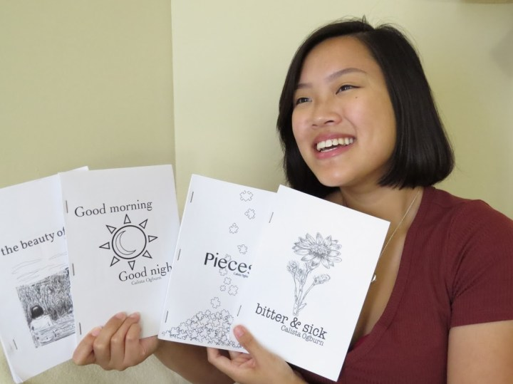 Young Asian woman holds up four small books. She smiles as she shows their covers.