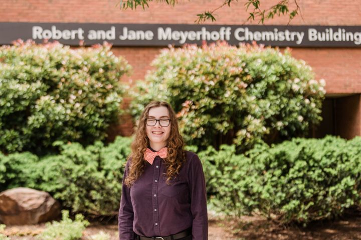 """Young adult with long, curly hair smiles for a portrait, wearing a dress shirt and bow tie. The sign behind them reads """"Robert and Jane Meyerhoff Chemistry Building."""""""