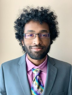 A young man with black curly hair with dark rimmed glasses wearing a grey suit jacket, pink dress shirt, and multicolored tie smiles as the camera.