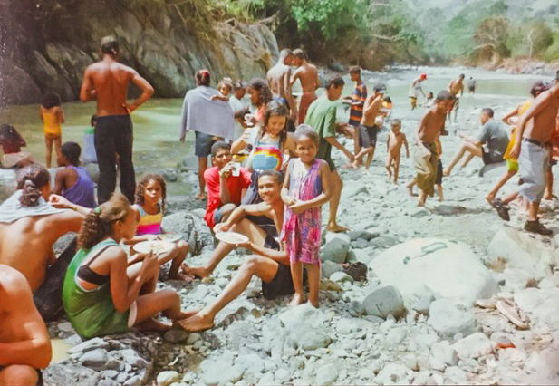 A large group of adults and children swim in a river on a sunny day.