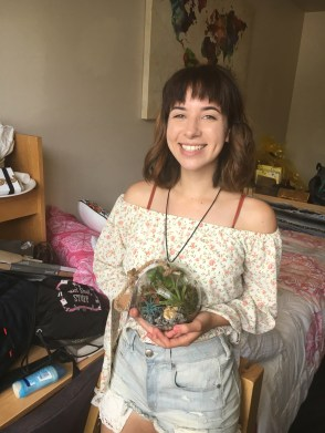 A young woman wearing an off the shoulder flow print blouse and jean shorts holds a glass bowl and smiles at the camera there is a bed and a desk in the background.