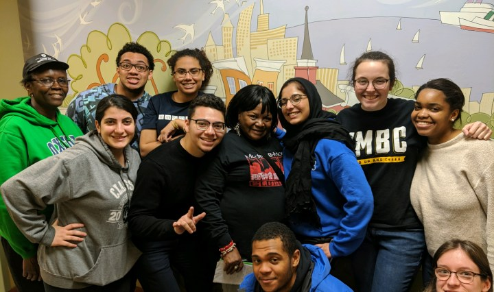 A group of eleven young men and women huddling together in front of a mural.