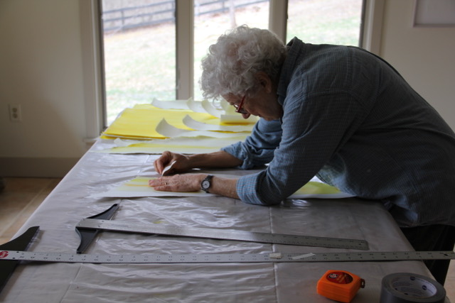 A woman with short, curly, white hair wearing a denim long sleeve shirt leans over a long table covered with white and yellow paper paper and long metal rulers.