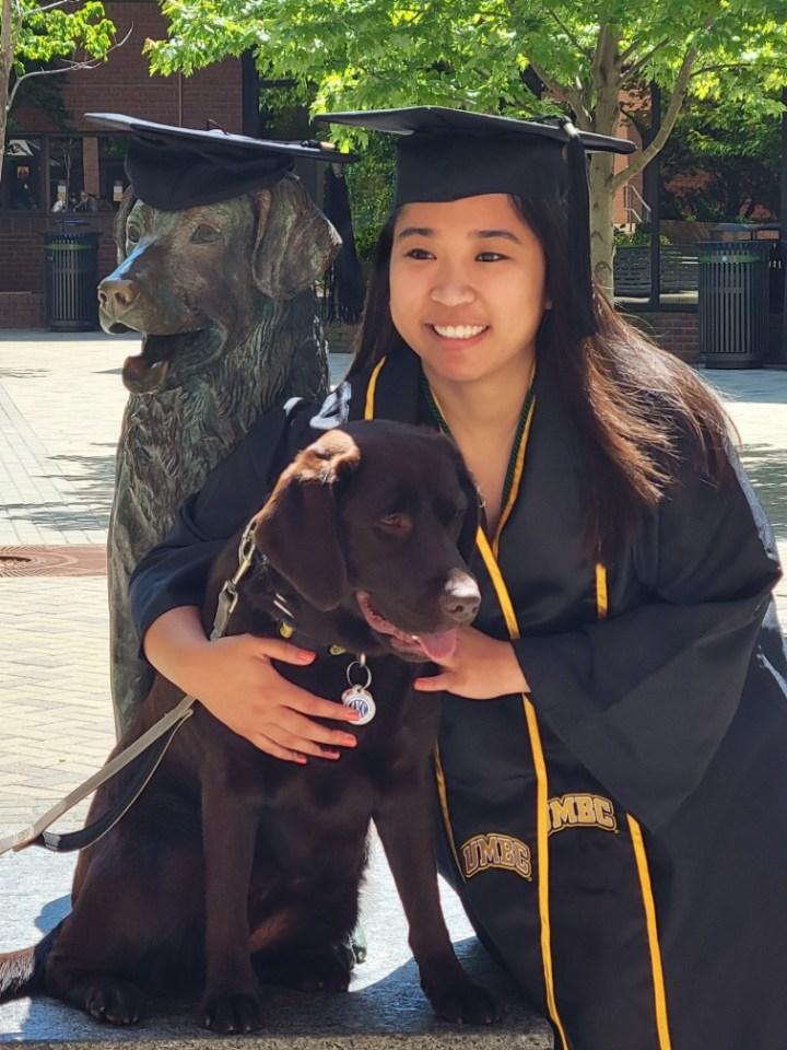 A woman wears graduation regalia, and holds a chocolate lab dog.