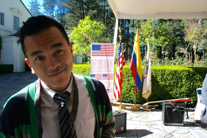 A young man with short black hair wearing a white collar dress shirt a black and white striped tie and a green, yellow, and black cardigan stands in front of three large flags of different colors.