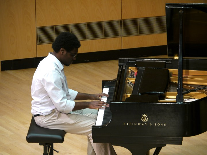 A young man plays a grand piano in a concert hall.