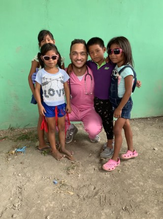 A smiling young man wearing pink scrubs and a stethoscope poses with four children, two in sunglasses.
