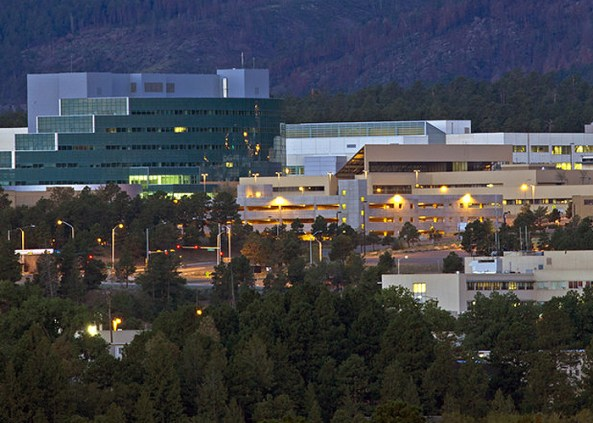 Modern-looking buildings surrounded by coniferous forest and hills, in the evening.