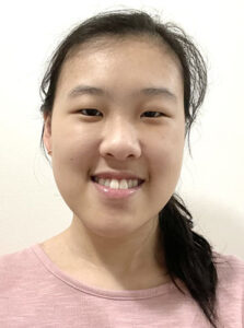 A young woman with long black hair pulled back in a pony tail wearing a light pink sweatshirt smiles at the camera.
