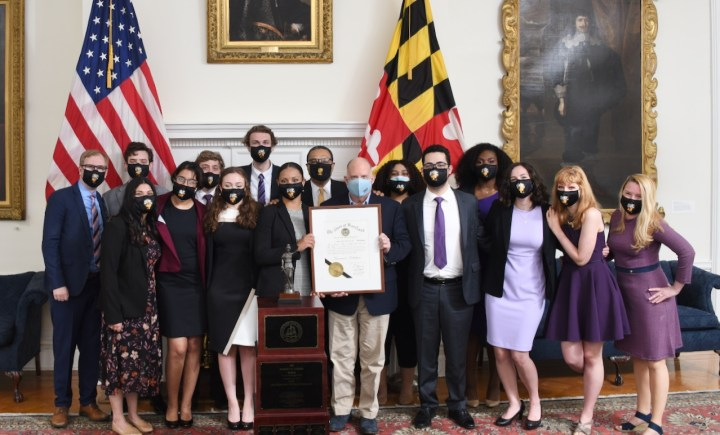 Over a dozen young adults and a few older adults in business attire stand in front of the US and Maryland flags, holding a framed document.
