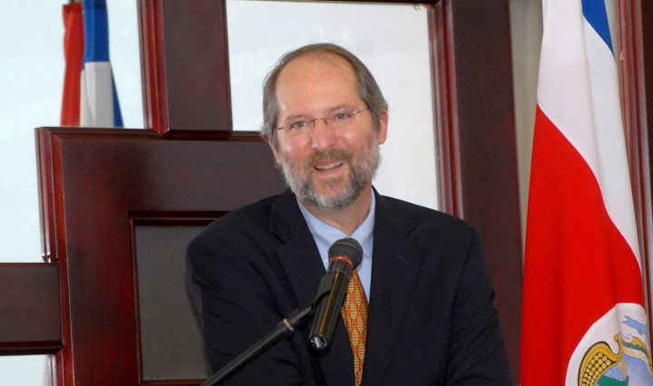 A man wearing a dark suit jacket, light blue dress shirt, and orange tie is seated and has a microphone in front of him.