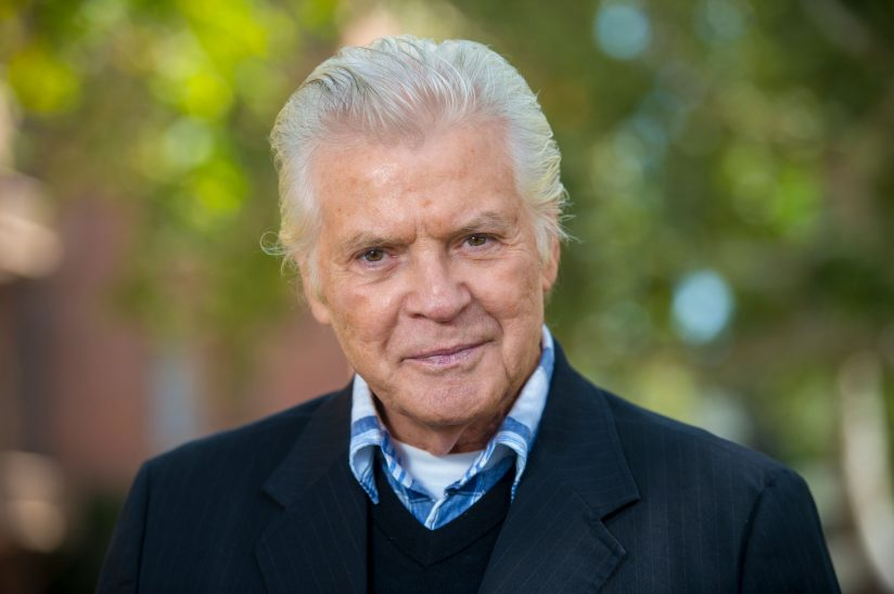 Teaching gerontology: George Shannon photographed in a headshot style photo outside in a courtyard at USC.
