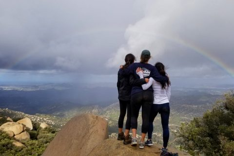 USC grad Marla Ross and friends standing on  a boulder overlooking a valley, a photo to help students find spots to explore.