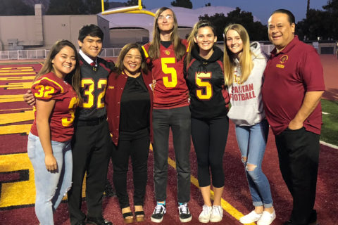The Shute siblings with the Lee family standing together at the USC football training field.