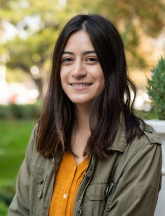 Environmental studies major Connie Machuca photographed sitting outside - she is smiling and looking into the camera.