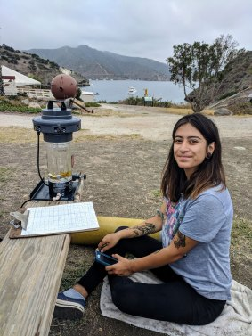 Environmental studies major Connie Machuca sitting outside in the Catalina camping grounds, with documents and notes in front of her.