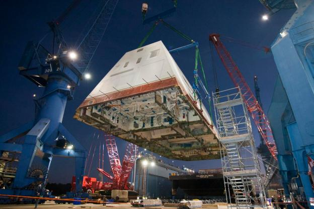 The 1,000-ton deckhouse of the future destroyer USS Zumwalt (DDG 1000) is craned toward the deck of the ship to be integrated with the ship's hull at General Dynamics Bath Iron Works on Dec. 14, 2012. US Navy Photo