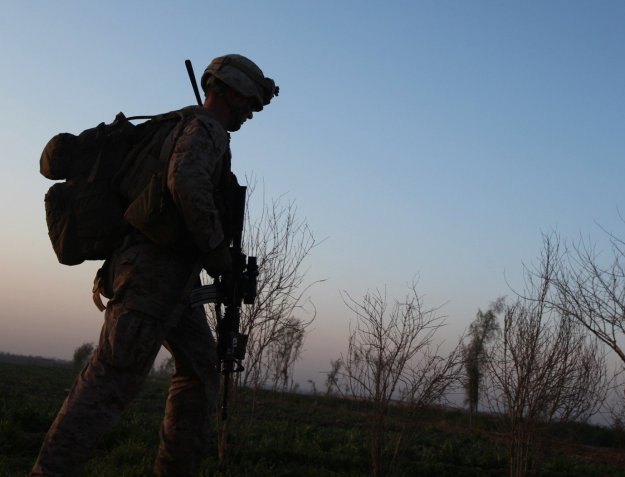 An infantry Marine with 3rd Platoon, Charlie Company, 1st Battalion, 9th Marine Regiment, walks across a field during a security patrol in Helmand province, Afghanistan, Feb. 20, 2014. US Marine Corps Photo