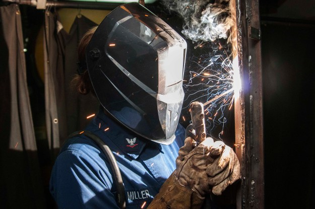 A sailor welds during the ongoing maintinance availability for carrier USS Dwight D. Eisenhower (CVN-69) on June 26, 2014. US Navy Photo