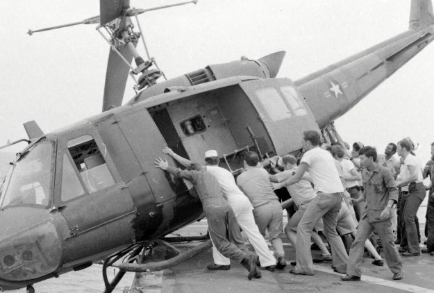 Personnel pus a UH-1 Iroquois off the deck of USS Kirk at the close of the Vietnam War.