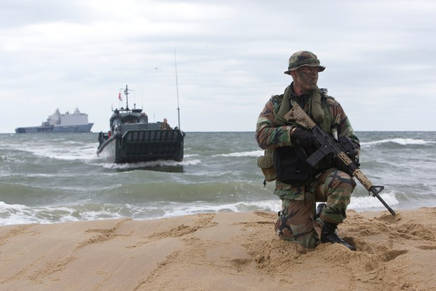 A Dutch marine from the Royal Netherlands Marine Corps is securing the area of Utah Beach during Bold Alligator 14. Dutch amphibious ship HNLMS Johan de Witt (L-801), in the background, served as the command and control headquarters during the exercise to improve interoperability between Dutch, American and other partners' militaries. US Navy photo courtesy of the Royal Netherlands Air Force.