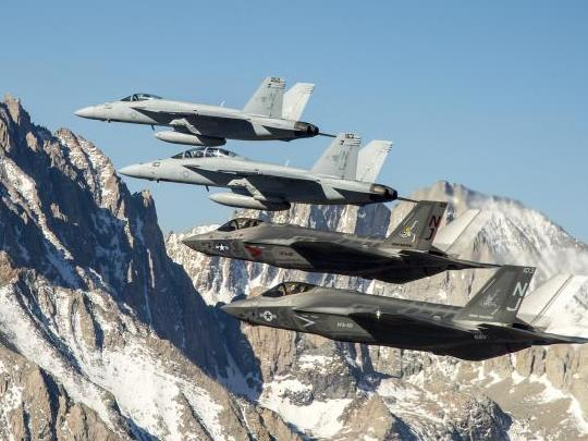 Two F-35C Lightning II aircraft fly in formation over the Sierra Nevada mountain range with to two F/A-18E/F Super Hornets from Naval Air Station (NAS) Lemoore. US Navy photo.