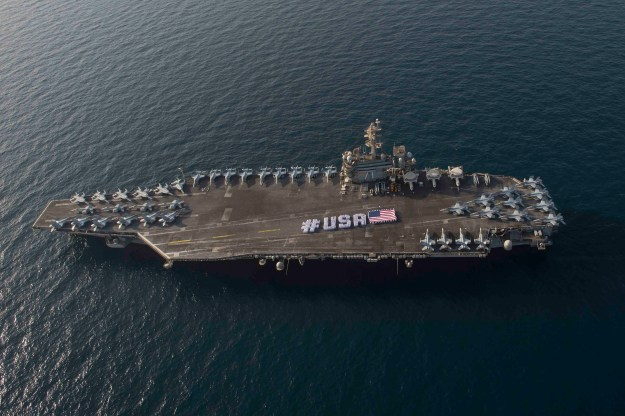 Sailors spell out #USA with the American flag on the flight deck of the aircraft carrier USS Theodore Roosevelt in honor of the nation's upcoming Independence Day weekend on June 28, 2015. US Navy Photo