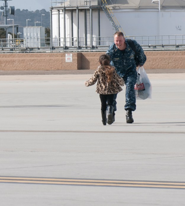 Senior Chief Information Systems Technician Dan Boemmel is greeted by his daughter after returning home from a deployment around South America. Aircraft carrier on Jan. 15, 2016. US Navy Photo