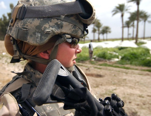 U.S. Army Sgt. Ashley Hort keeps her weapon at the ready as she provides security for her fellow soldiers during a raid in Al Haswah, Iraq, on March 21, 2007. US Army Photo