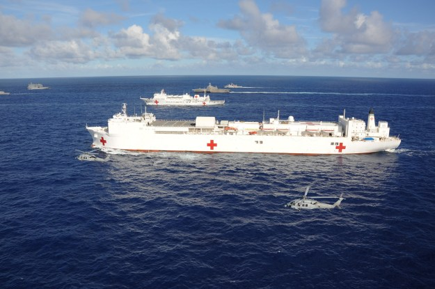 An MH-60S Sea Hawk helicopter assigned to the Black Knights of Helicopter Sea Combat Squadron (HSC) 4 operates near the Military Sealift Command hospital ship USNS Mercy (T-AH 19) and the People's Republic of China medical ship Peace Ark (T-AH 866) during a close formation of 42 ships and submarines from 15 international partner nations during Rim of the Pacific (RIMPAC) 2014. US Navy photo.