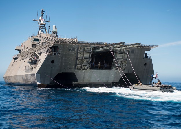 Sailors assigned to Surface Warfare Mission Package Detachment 2 prepare to be hoisted out of the water by the littoral combat ship USS Coronado's (LCS 4) twin-boom-extensible crane following a visit, board, search and seizure training exercise on Aug. 15, 2015. US Navy photo.