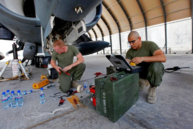 U.S. Marines Lance Cpl. Jason D. Launder, left, an avionics technician and Cpl. Noe L. Munoz, a collateral duty inspector, both with Marine Attack Squadron 311, troubleshoot and replace the landing gear system on an AV-8B Harrier. US Marine Corps Photo