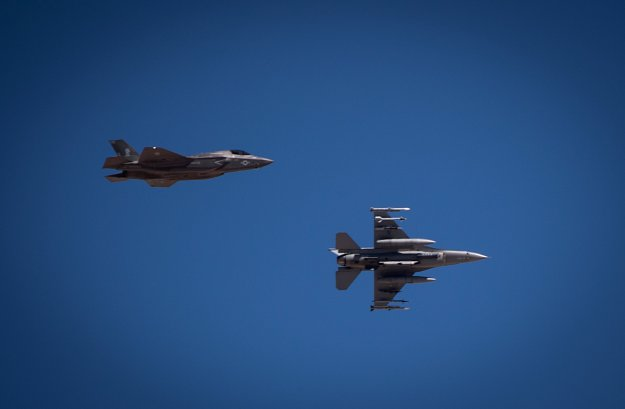 A F-35B, assigned to the Marine Fighter Attack Squadron 121 out of Marine Corps Air Station Yuma, Arizona, flies level as a F-16 Fighting Falcon from the 177th Fighter Squadron from the New Jersey Air National Guard, banks hard during approach July 15, 2016 at Nellis Air Force Base, Nevada. US Air Force Photo
