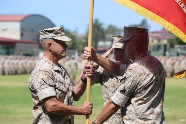 Lt. Gen. David H. Berger, the outgoing commanding general of I Marine Expeditionary Force, passes the unit colors to Lt. Gen. Lewis A. Craparotta during a change of command ceremony at Camp Pendleton on July 27, 2016. US Marine Corps Photo