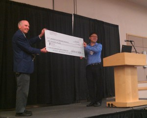 Hyeonsup Lim, right, a PhD candidate in the College of Engineering's Department of Civil and Environmental Engineering, receives a check for $2,000 from the Intelligent Transportation Society of Tennessee.