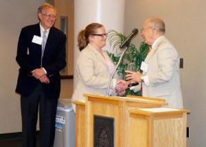Carl Pierce, left, looks on as Jerry Black presents the Black-Pierce Award to Brooke Burke.