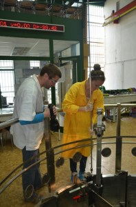 UT student Emily Frame rearranges the fuel in the core of a reactor at Czech Technical University in Prague while an instructor oversees and inspects the process.