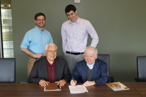 John Spitznagel, seated left, and Richard Hopkins sign funding for the UT program as Professor Ben Blalock, left, and Assistant Professor Daniel Costinett watch.
