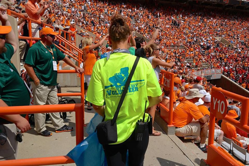 A UT Recycling team member collects recyclable materials during a football game.