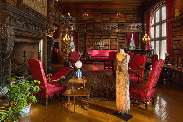 Lady Mary Crawley stands in Biltmore's library in a dusty-pink silk evening dress that was worn at dinner the first time Sir Richard visits Downton Abbey. Photo Credit: The Biltmore Company