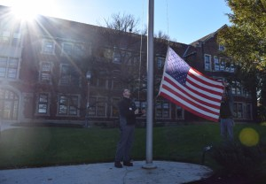 Maintenance Specialist Glenn McDowell and Maintenance Foreman Johnny Waggoner raising an American flag in front of Morgan Hall on the agriculture campus.
